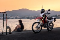 girl sitting at the edge of the dock near motocross bike during day