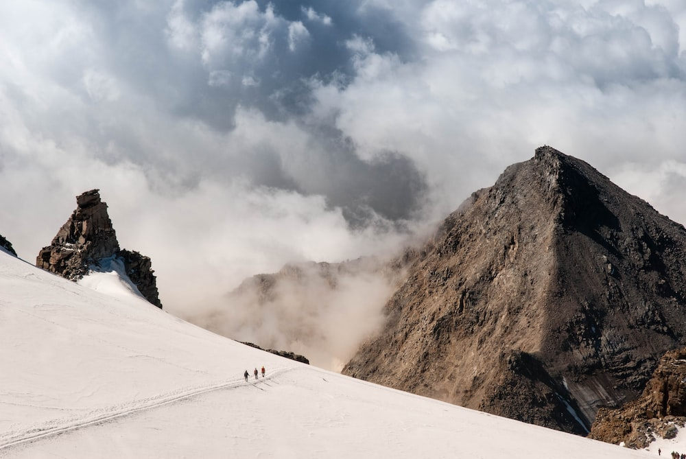 people walking on mountain alps with clouds