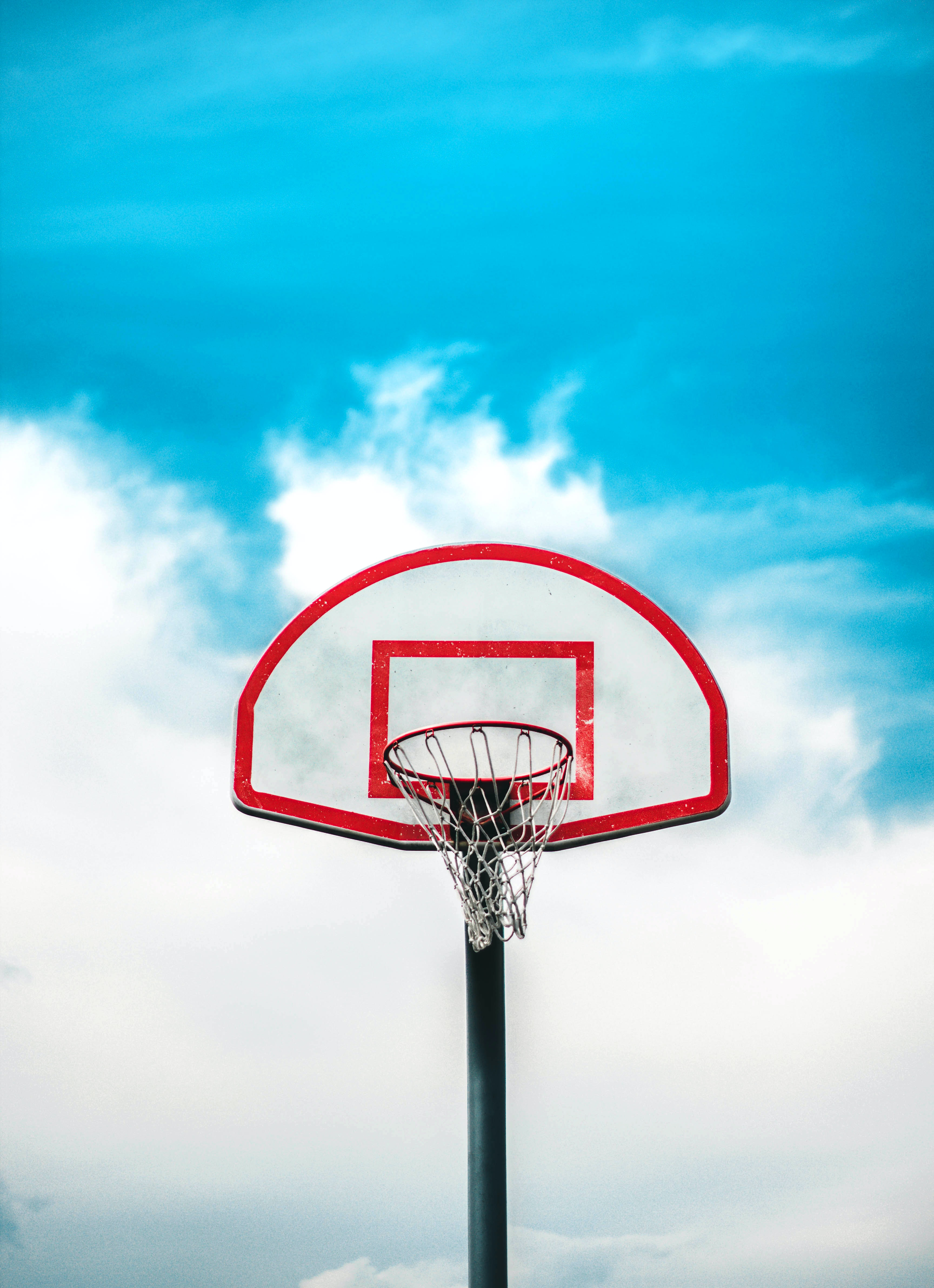 red and black basketball hoop under cloudy sky