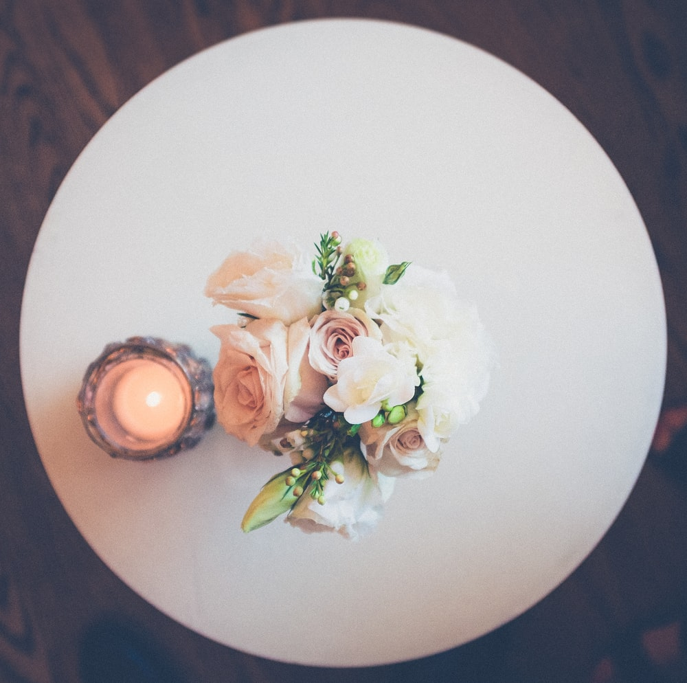 white rose flowers beside lighted candle on round white plate