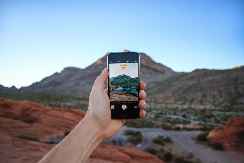person taking a picture of mountain