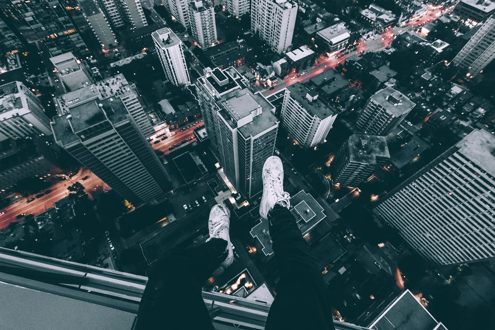 aerial photography of man sitting on top of building with high rise buildings view at daytime