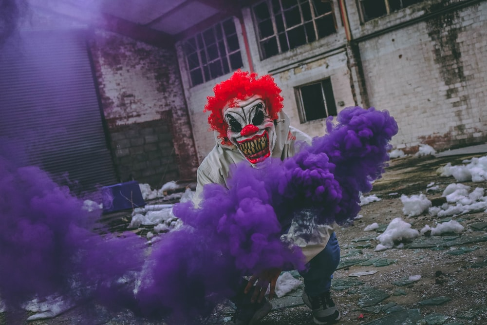 clown holding purple smoke bomb in ruined building