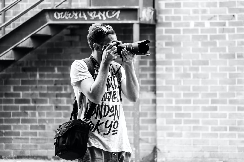 man capturing photograph with DSLR camera standing near stairway