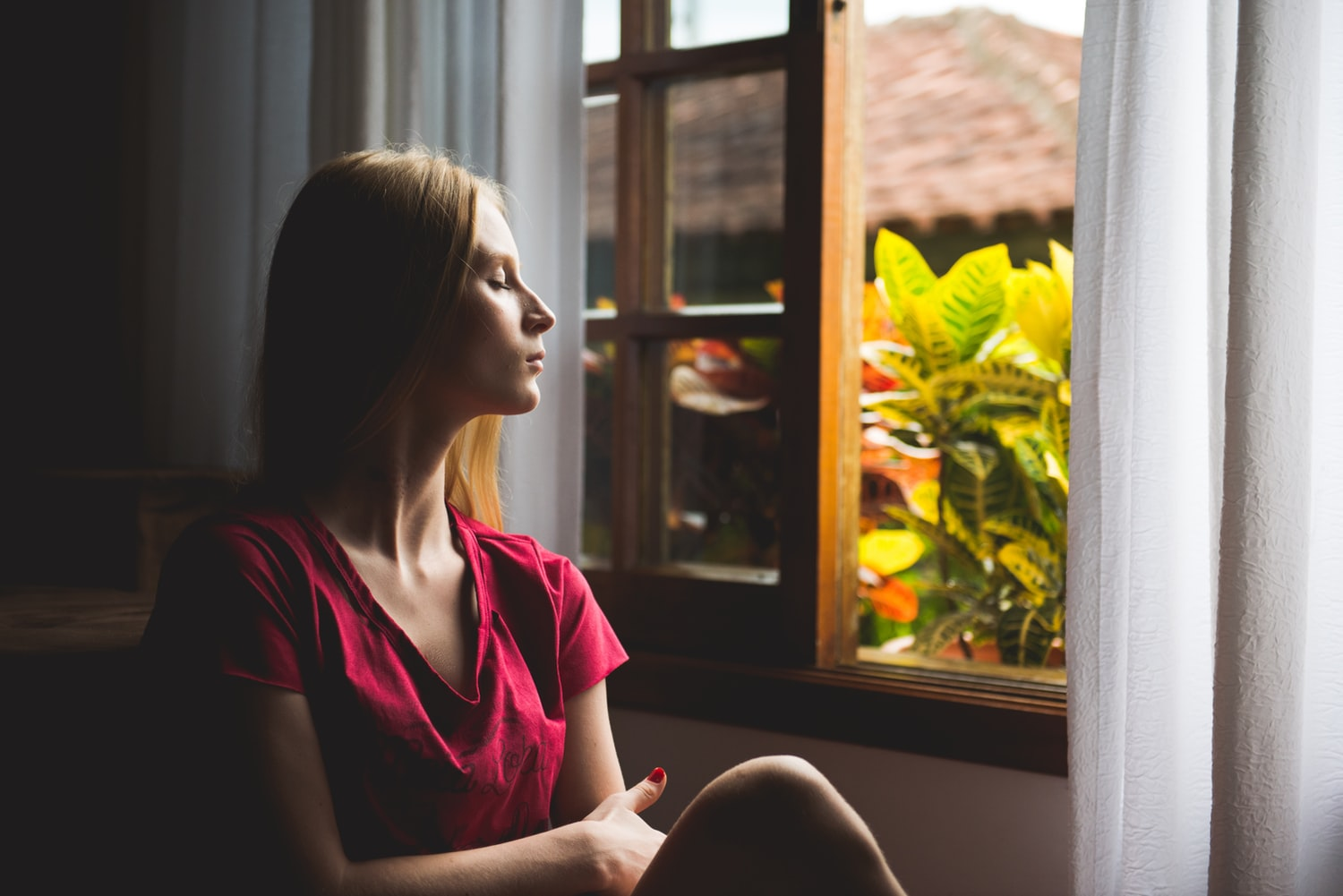 woman sitting at window calmly breathing and meditating