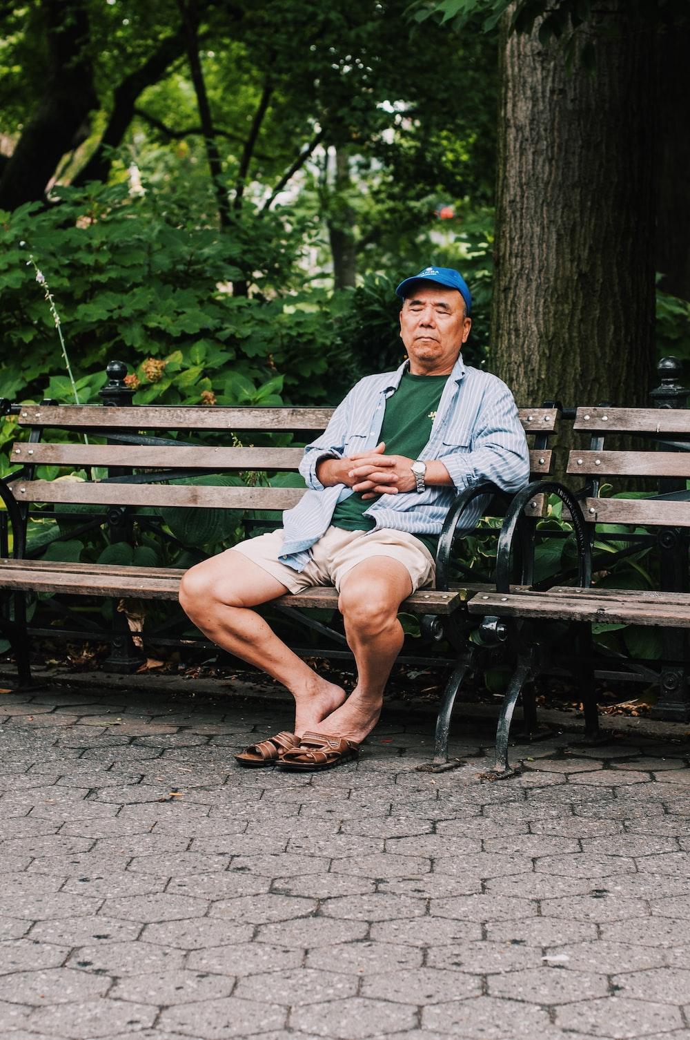 man sitting on bench closing his eyes near trees