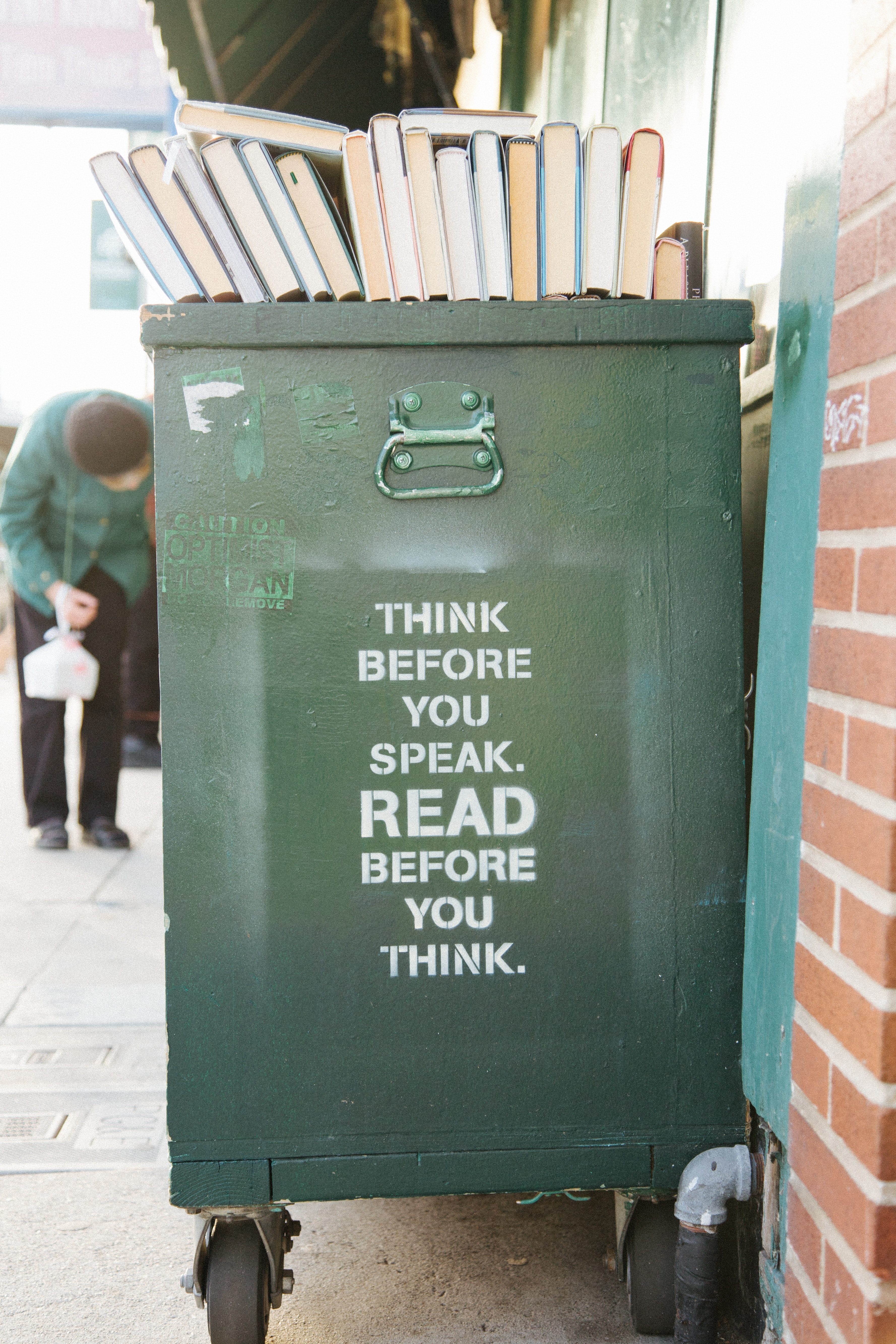 books over green trolley bin