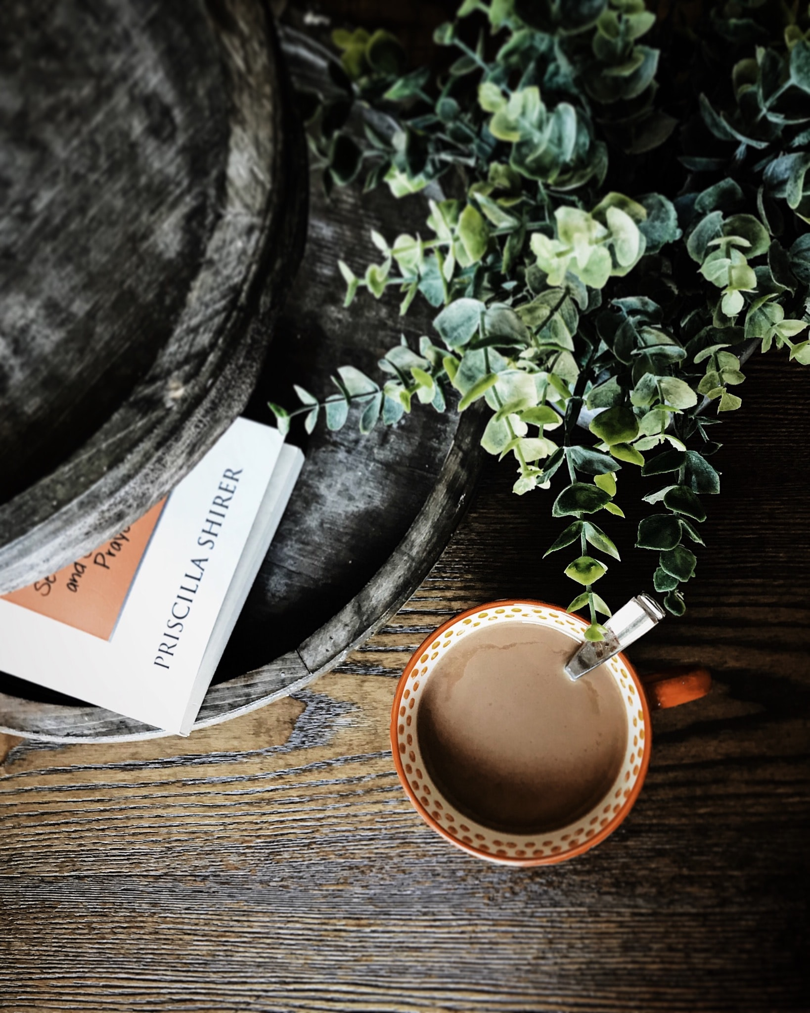 flat lay photography of coffee cup beside plant and book