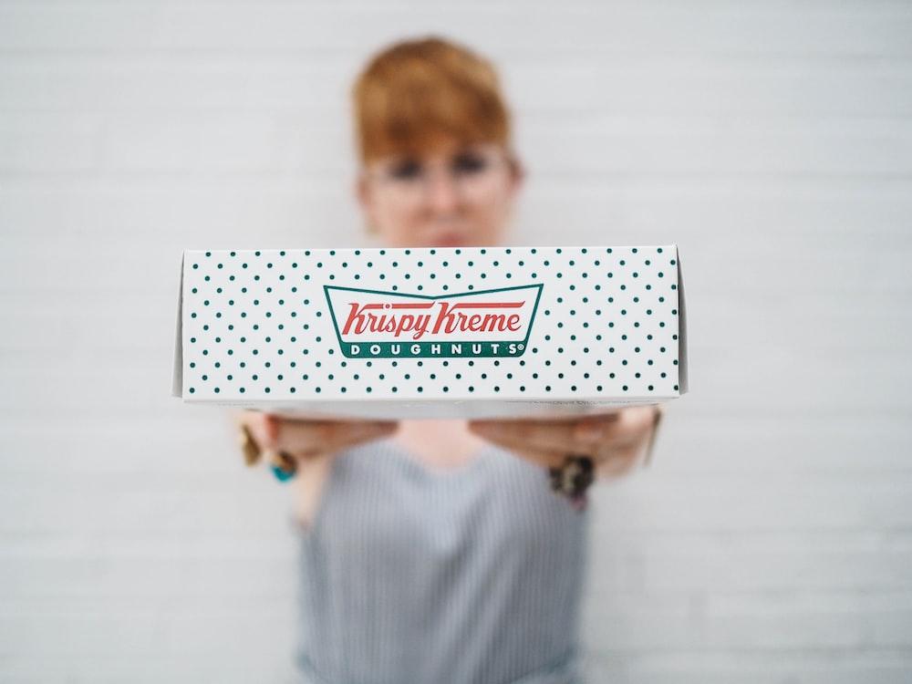 woman showing Krispy Kreme box
