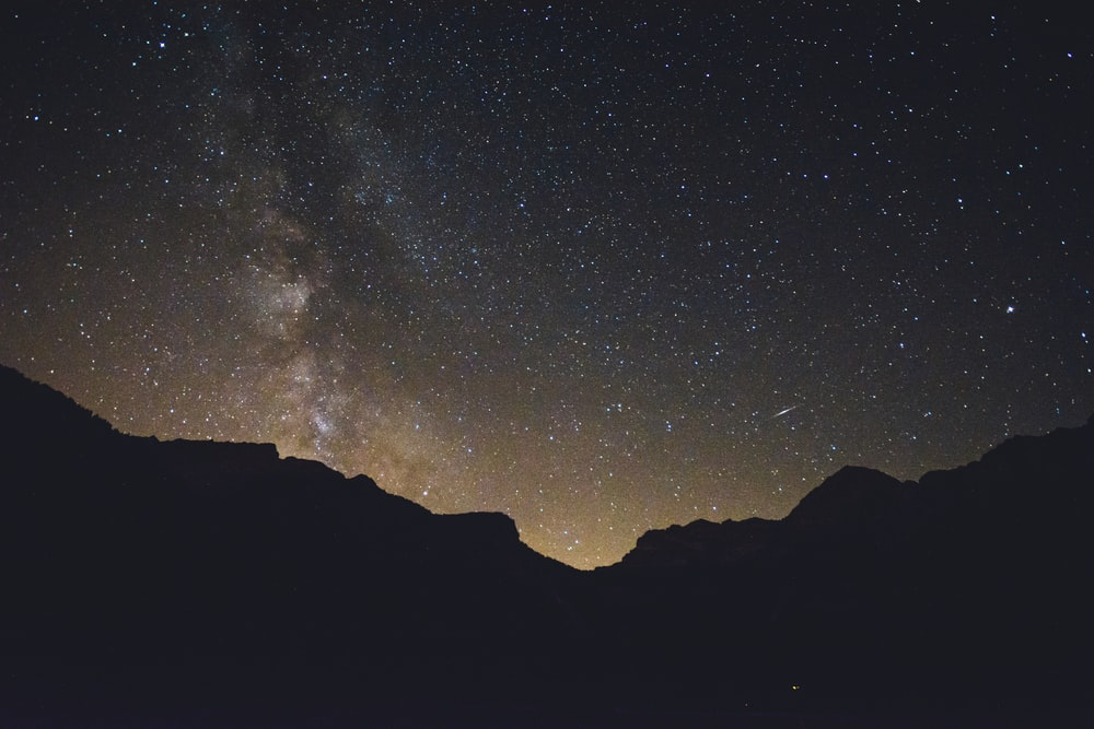 mountain silhouette under stars at nighttime
