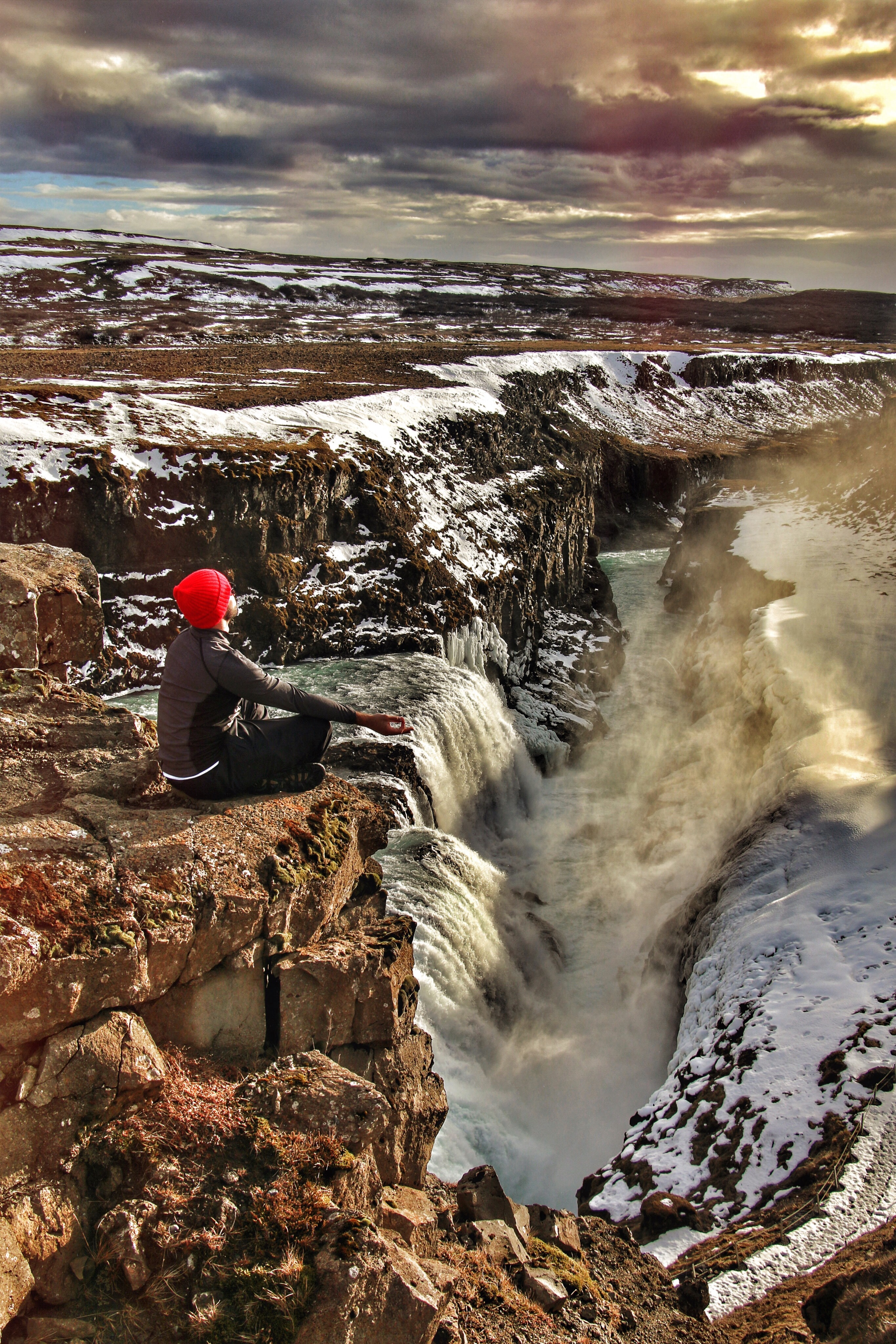 person sitting on top of multi-step waterfalls