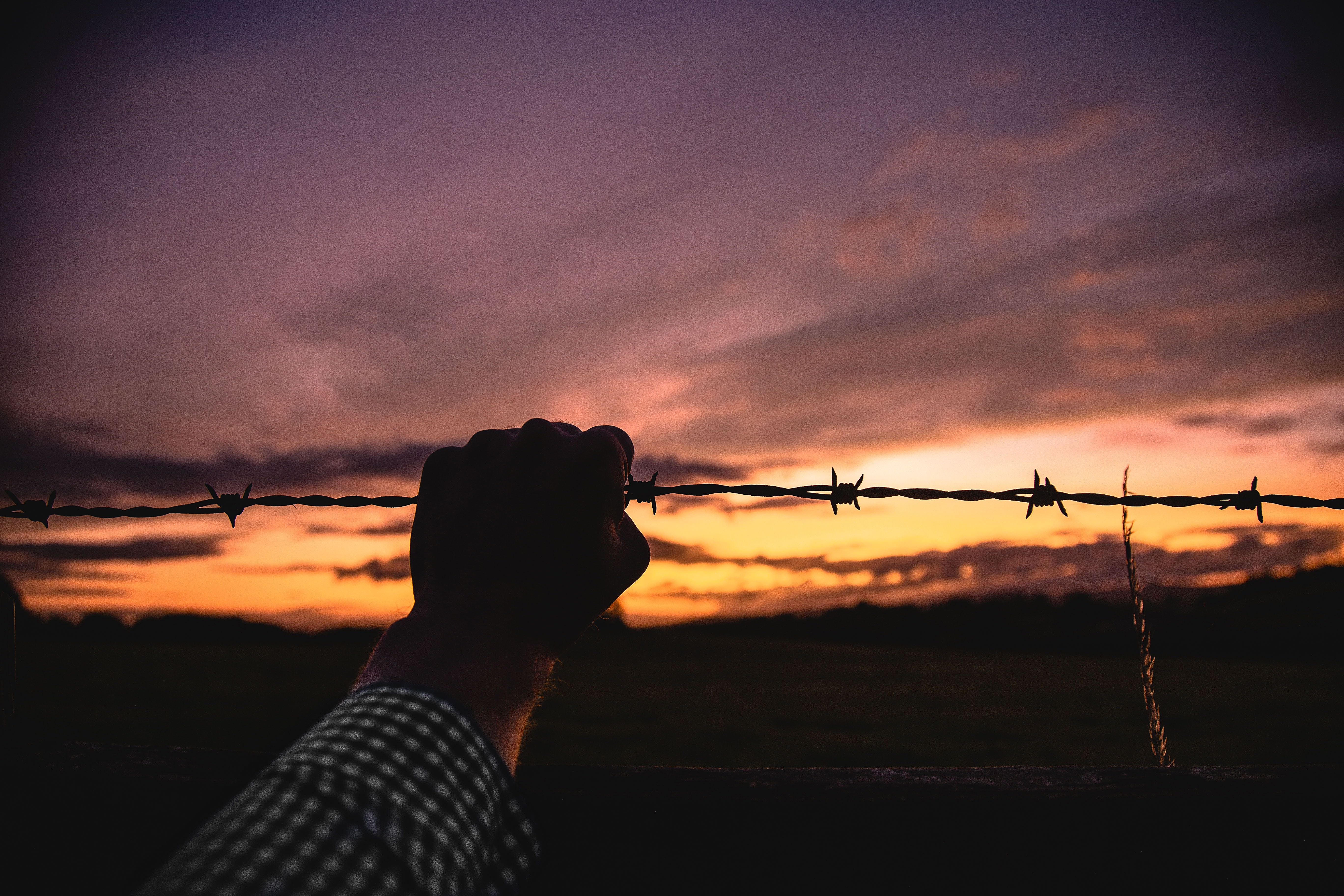 person holding barb wire