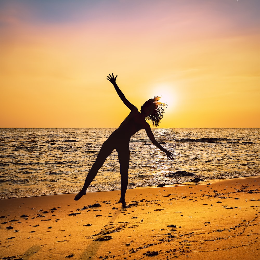 A woman about to do a cartwheel on the beach.