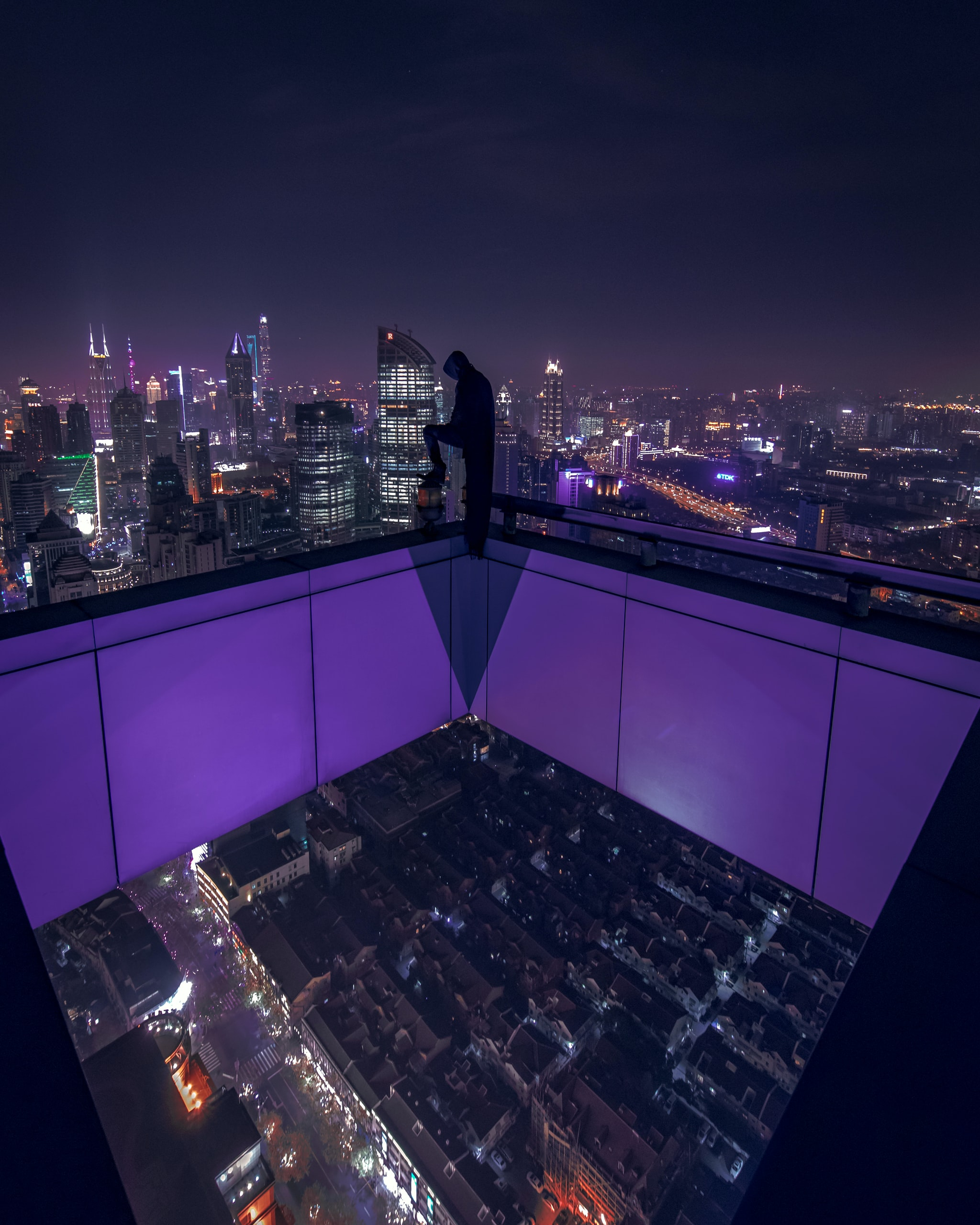 man standing on building rooftop during nigh time