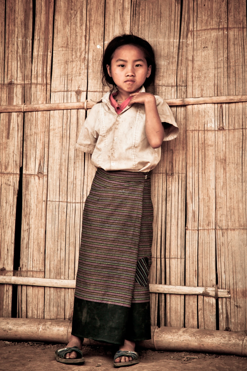 girl standing leaning on house's wall