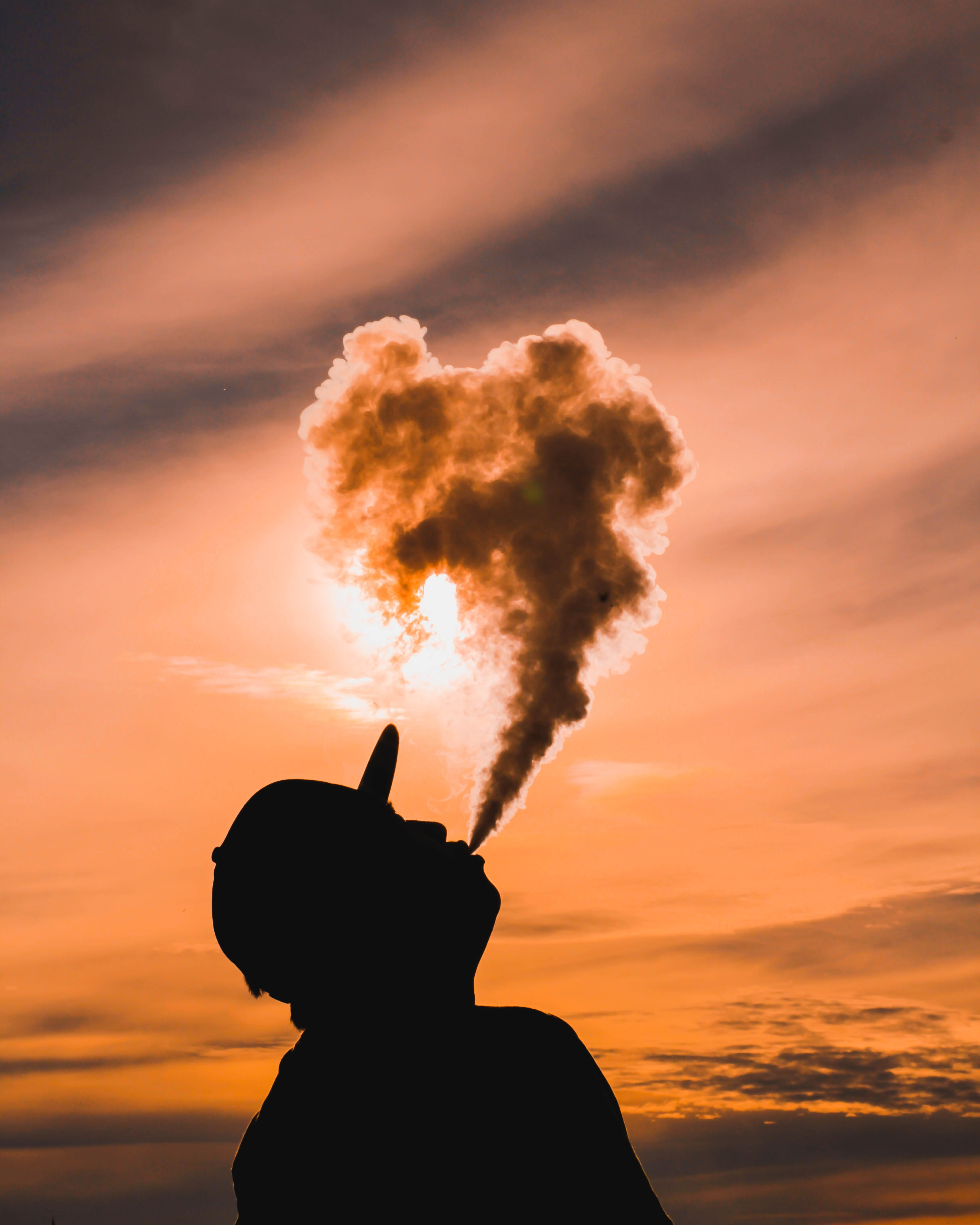 A person blowing smoke up into the air during a sunset.