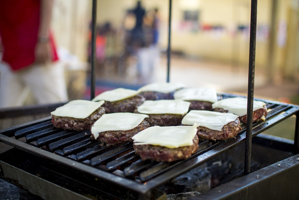 selective focus photography of meat patty with cheese on grill