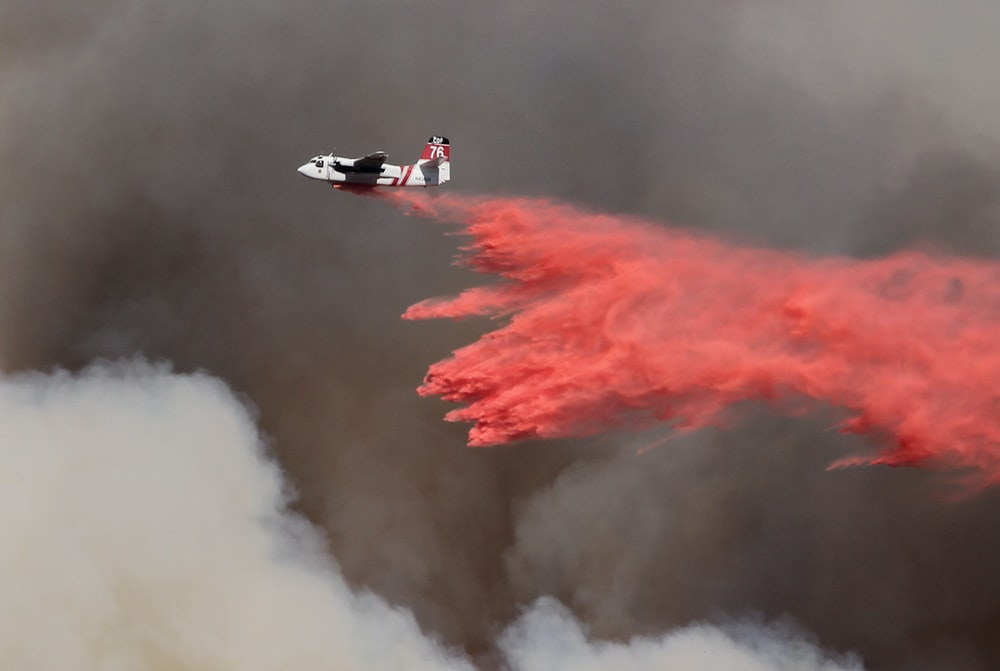 white and red airplane pouring red powder on fire