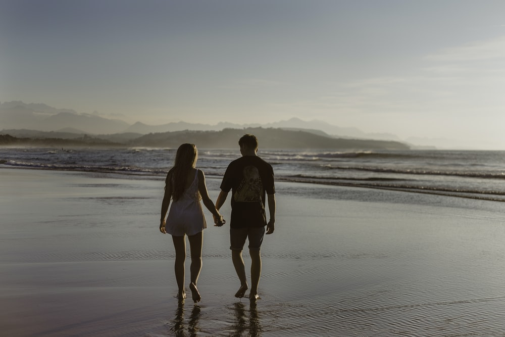 man and woman holding hands while walking on body of water