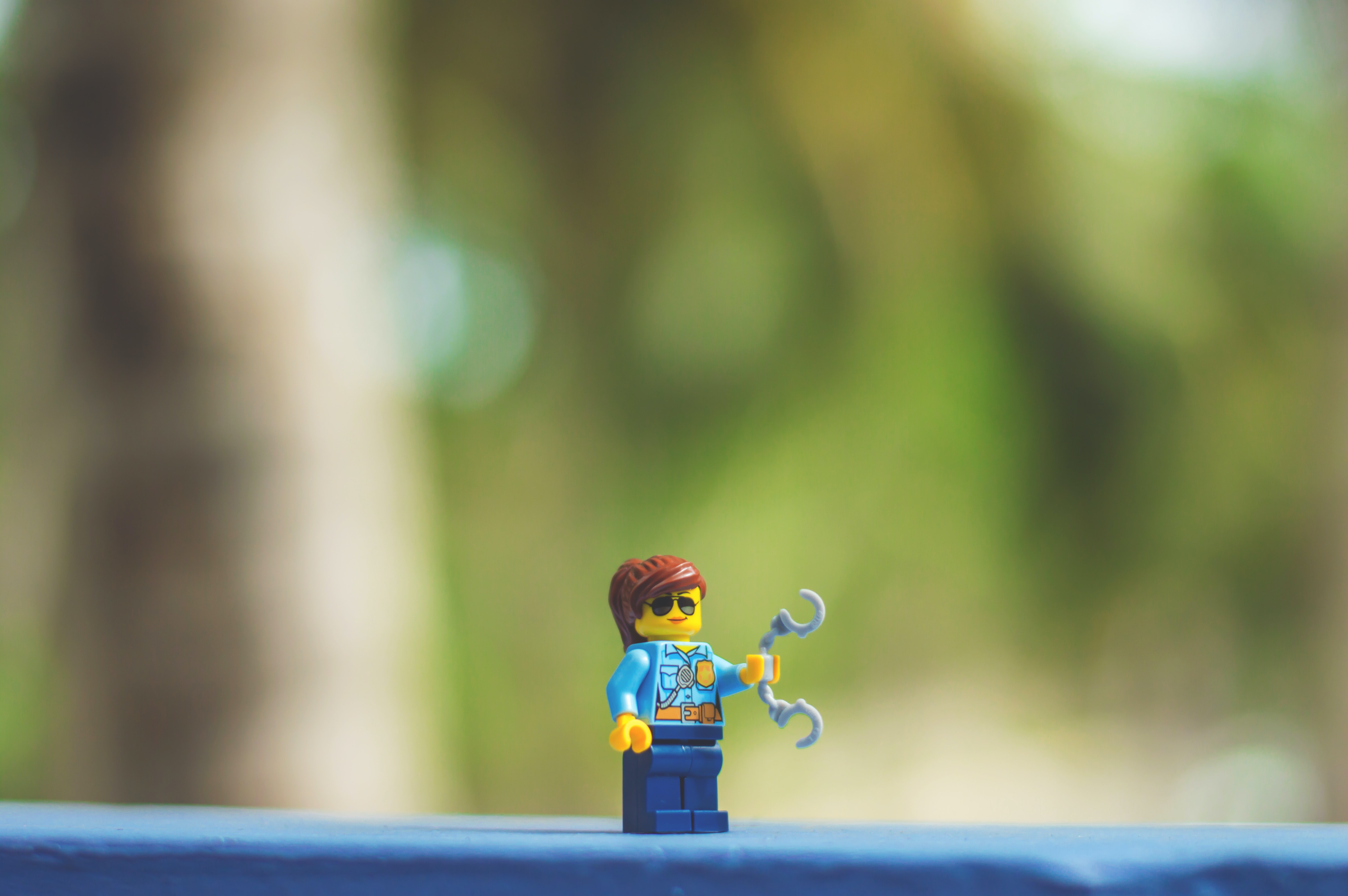 A little police officer Lego character holding handcuffs.