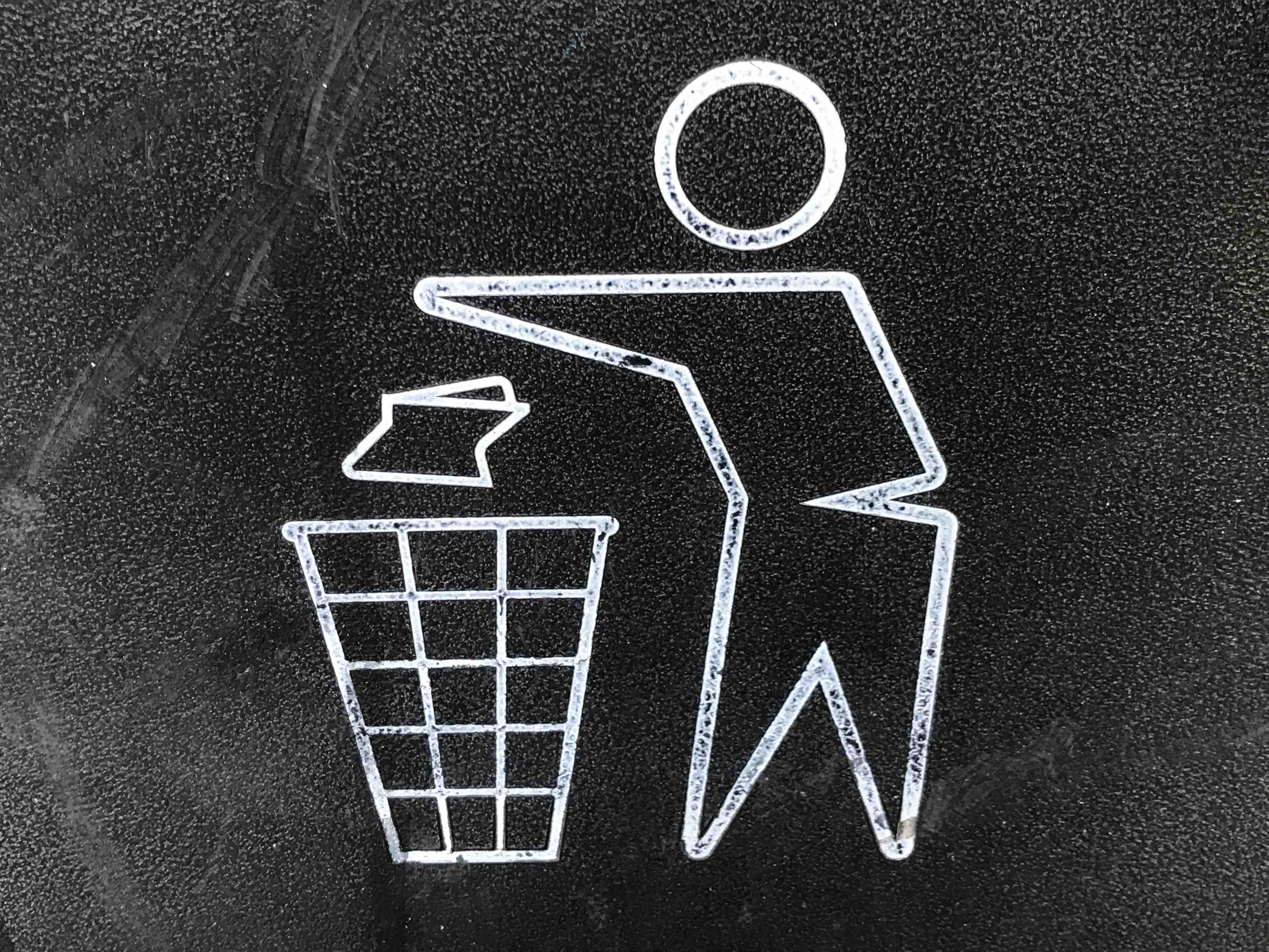 A chalk drawing of a person throwing garbage into a basket.