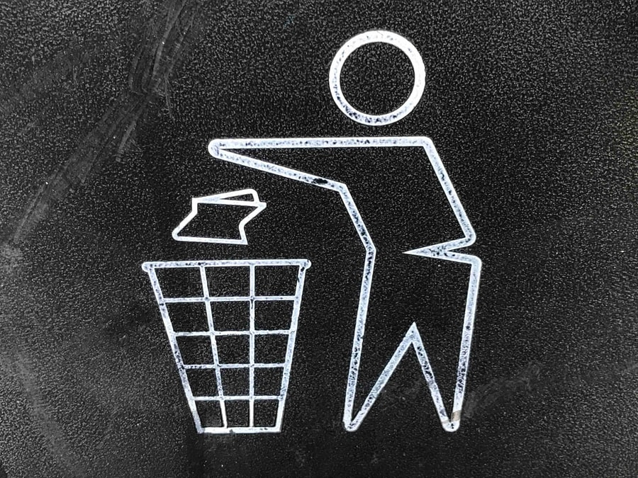A recycling bin logo showing a stylized person throwing a piece of paper into a wastebasket.