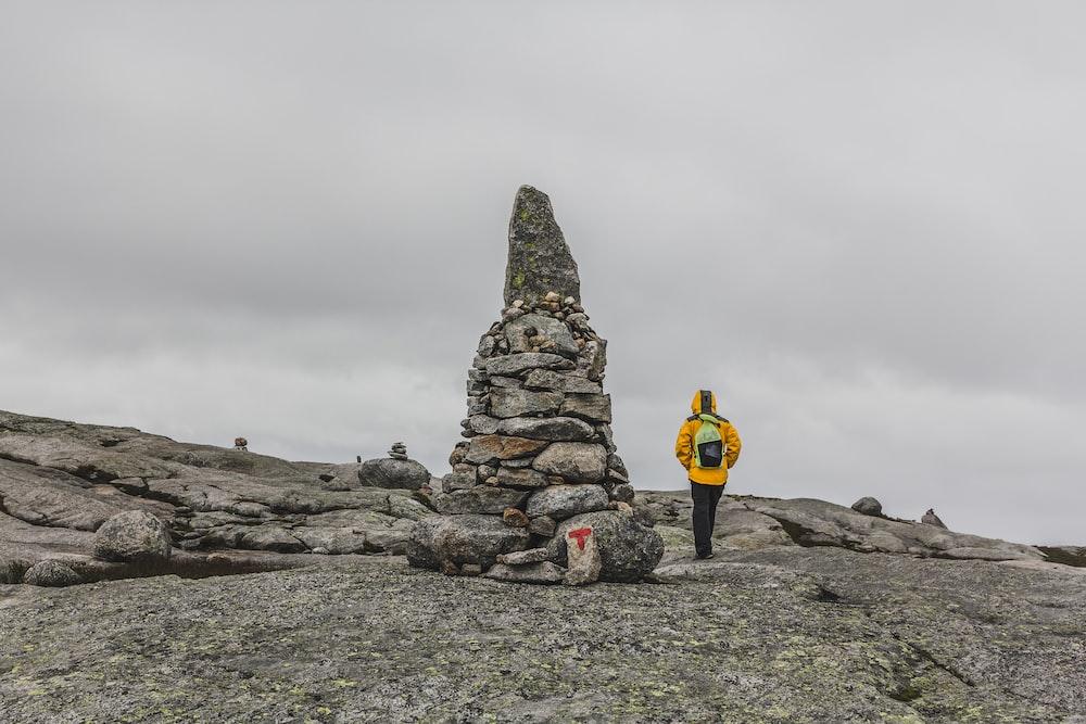 man walking beside rock formation under gray sky