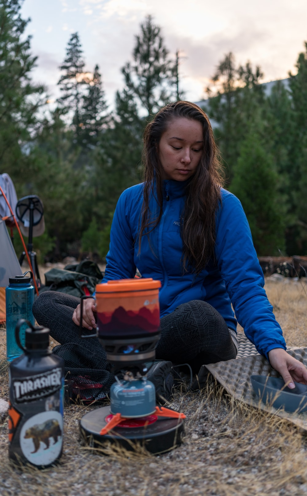 woman sitting on ground with camping stove and mat