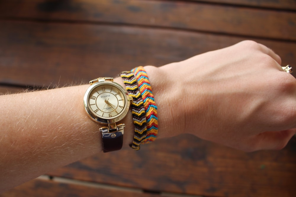 person wearing gold-colored analog watch with black strap