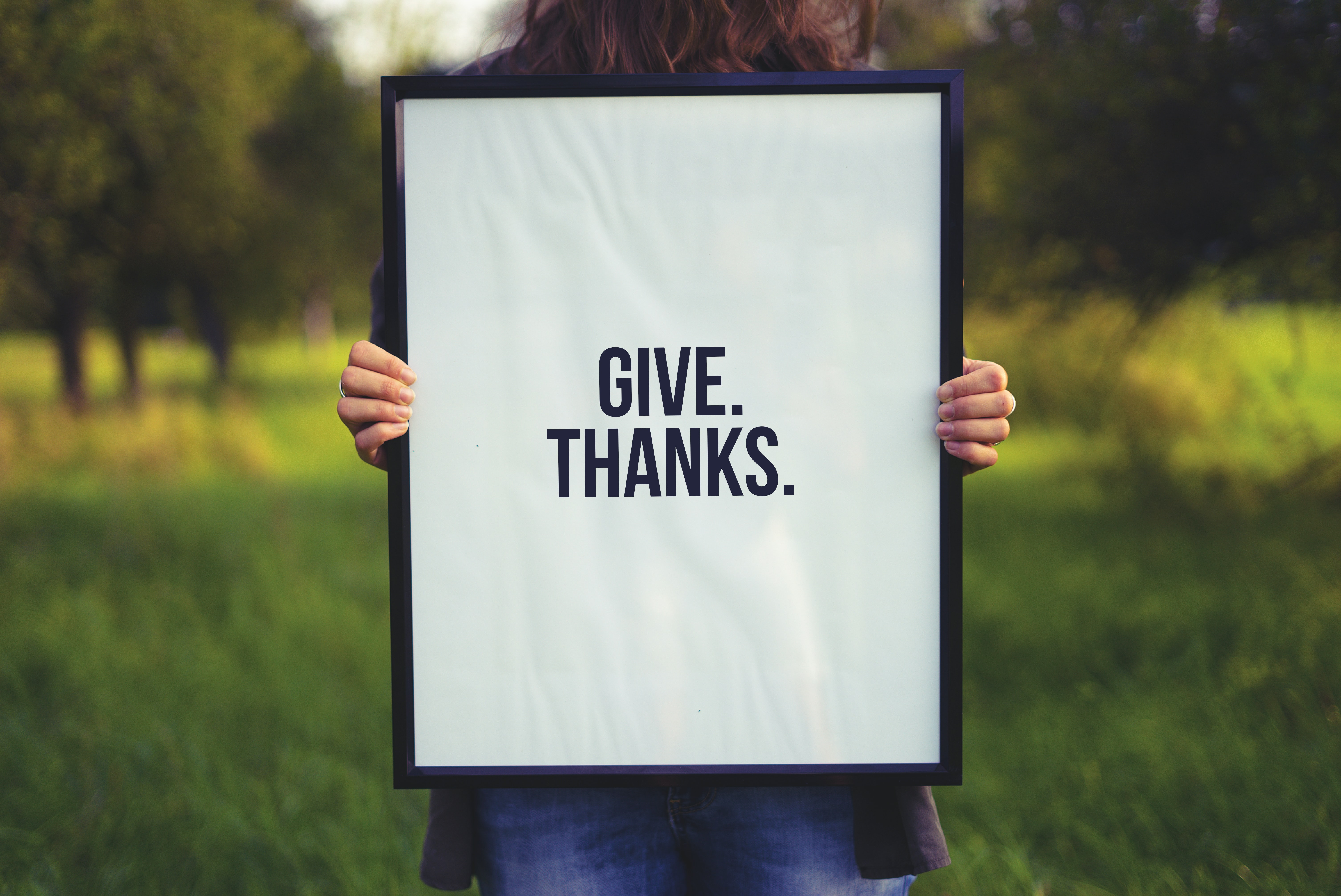 """A woman holding a sign that says """"give. thanks."""" on it in Werdorf"""