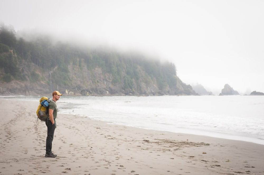 person carrying backpack standing on sea shore
