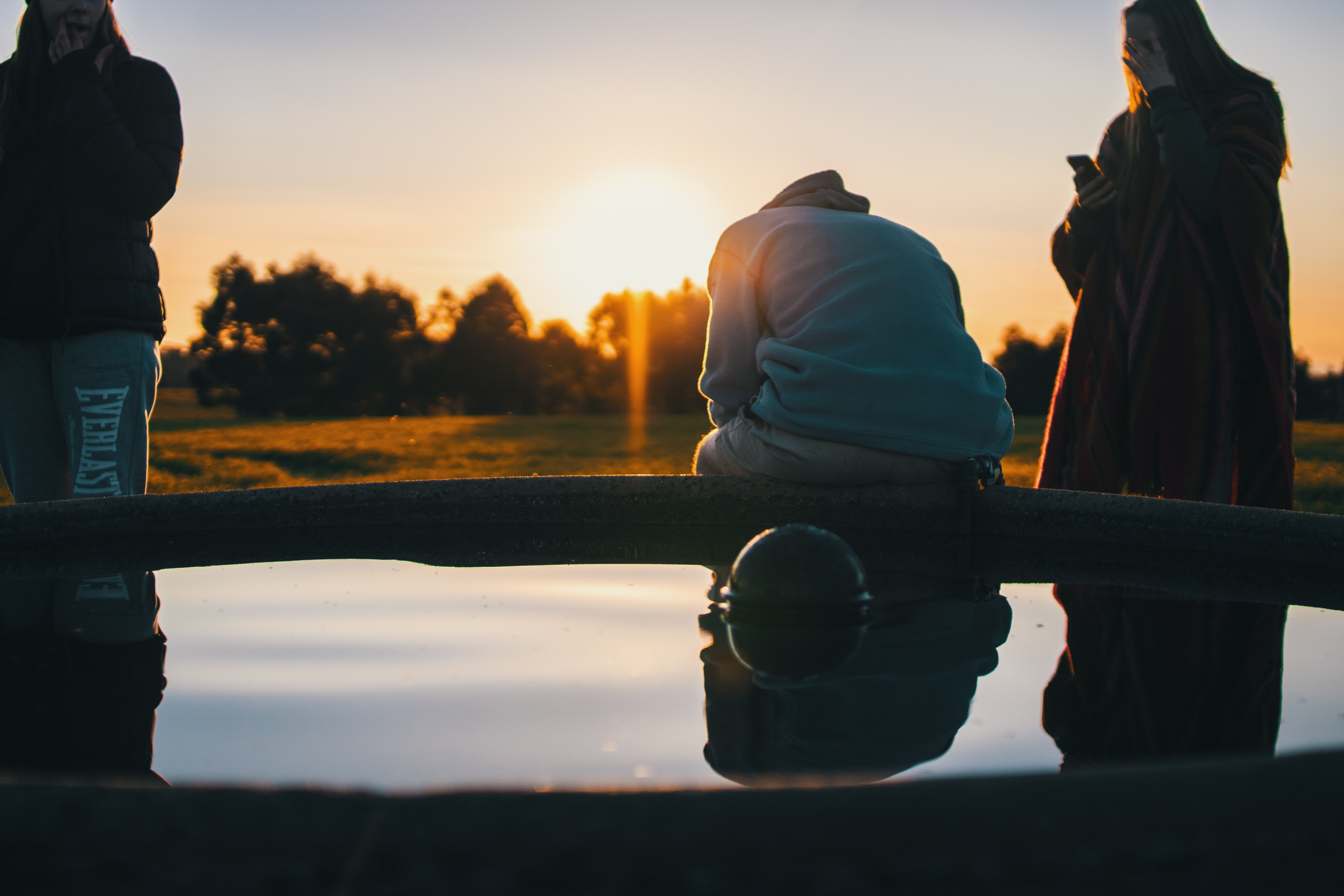Friends sit near a reflection pond in the country at sunset