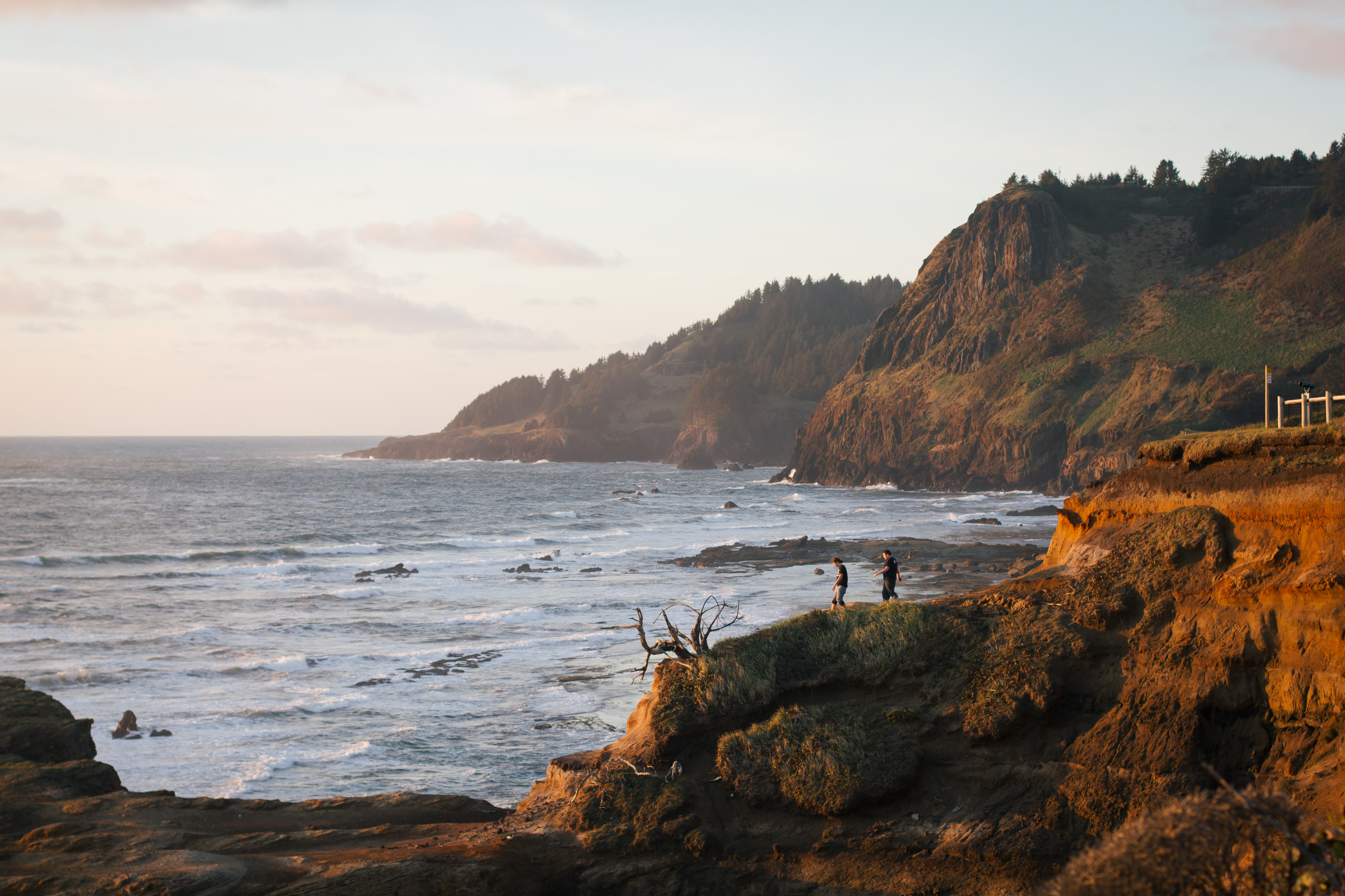 People on a rocky coastline, watching the water at dusk