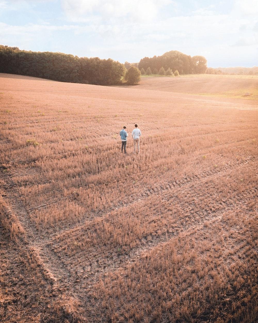 two men standing on ranch field