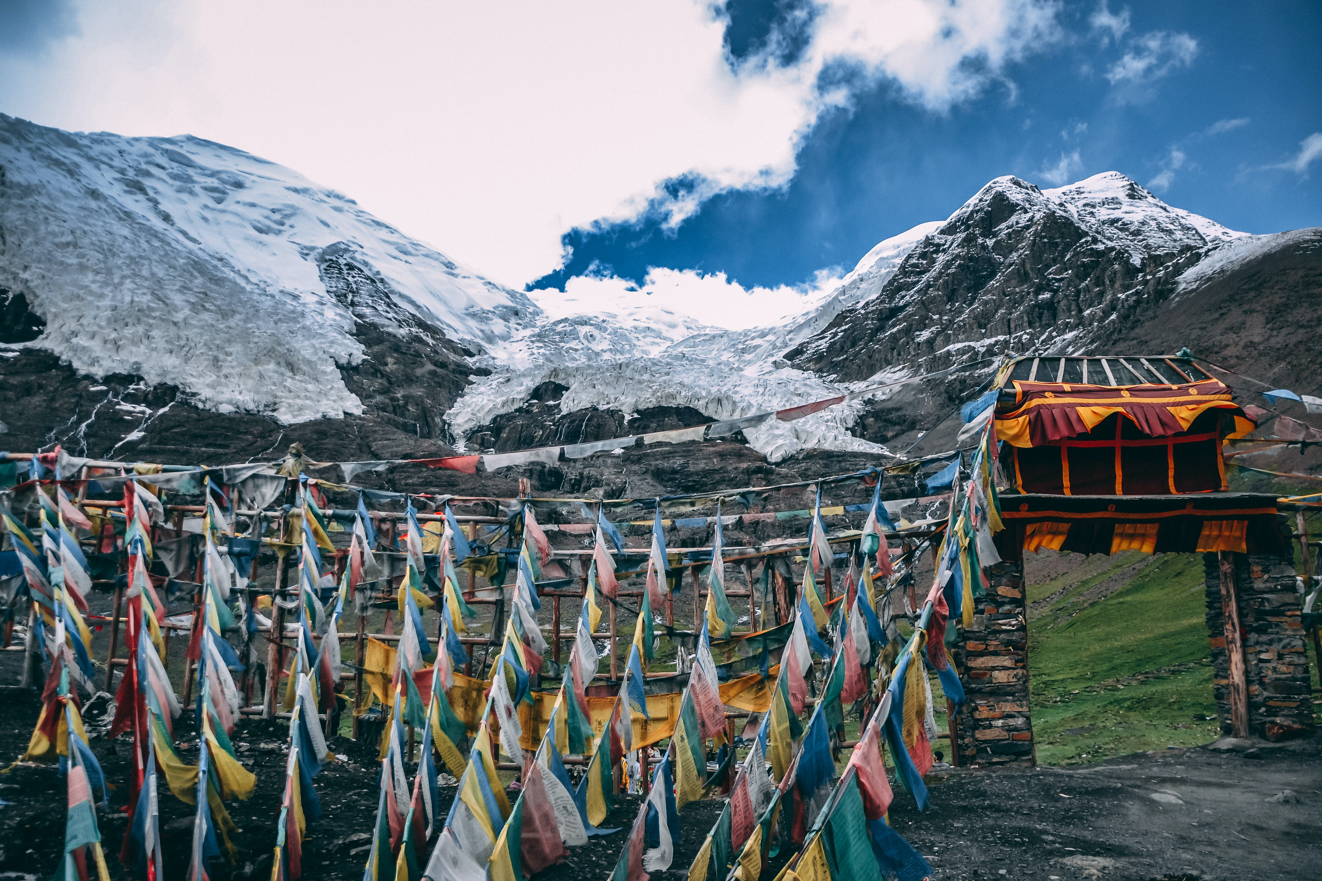 Colorful flags near a stone entryway to a mountain landscape in Tibet