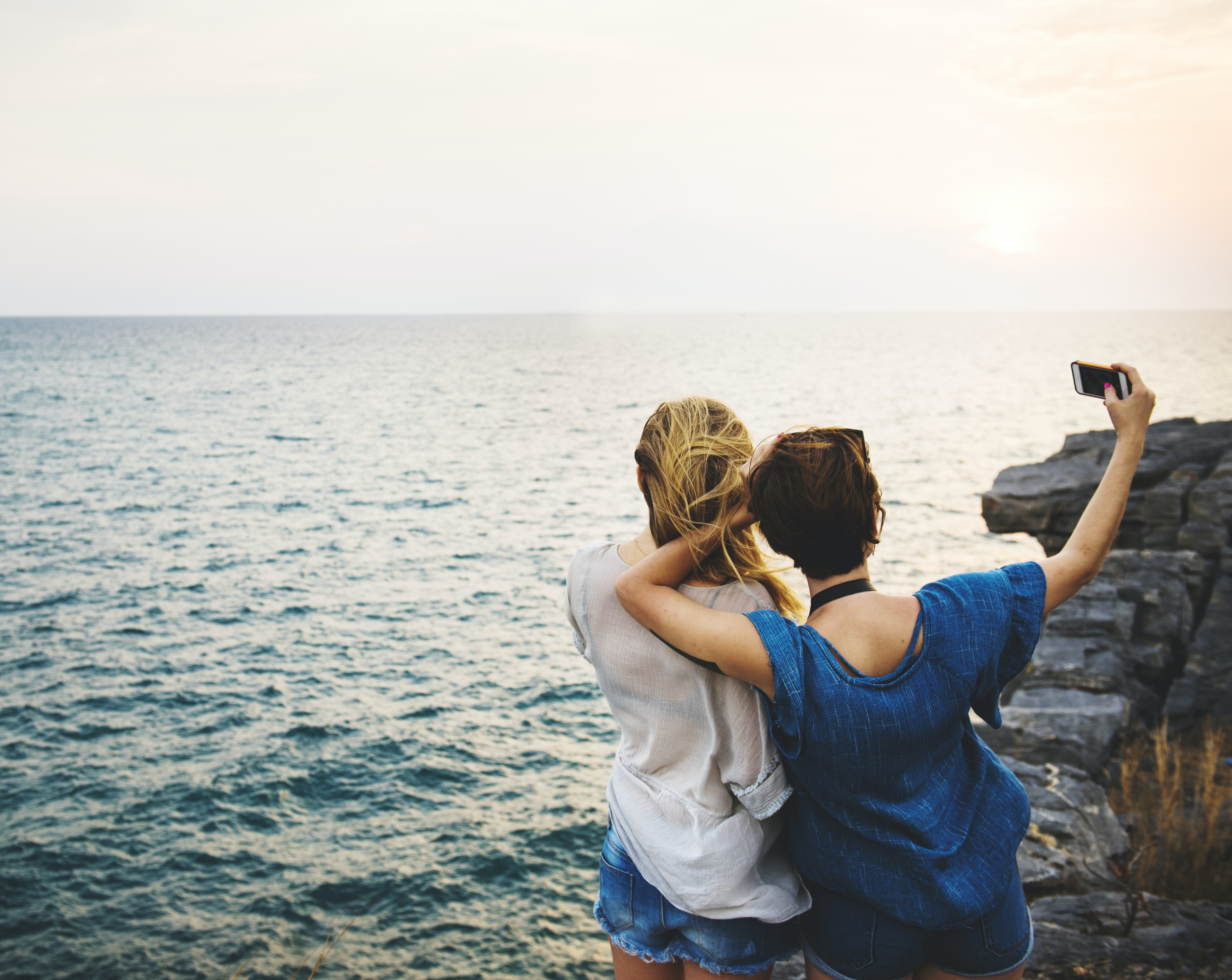 two woman standing near ocean during daytime