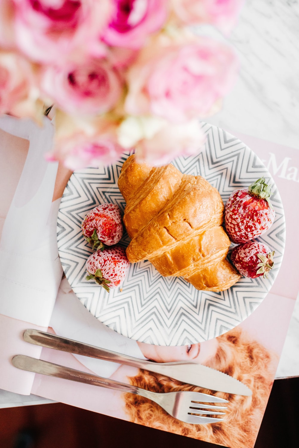 croissant bread and stawberries on beside fork and knife