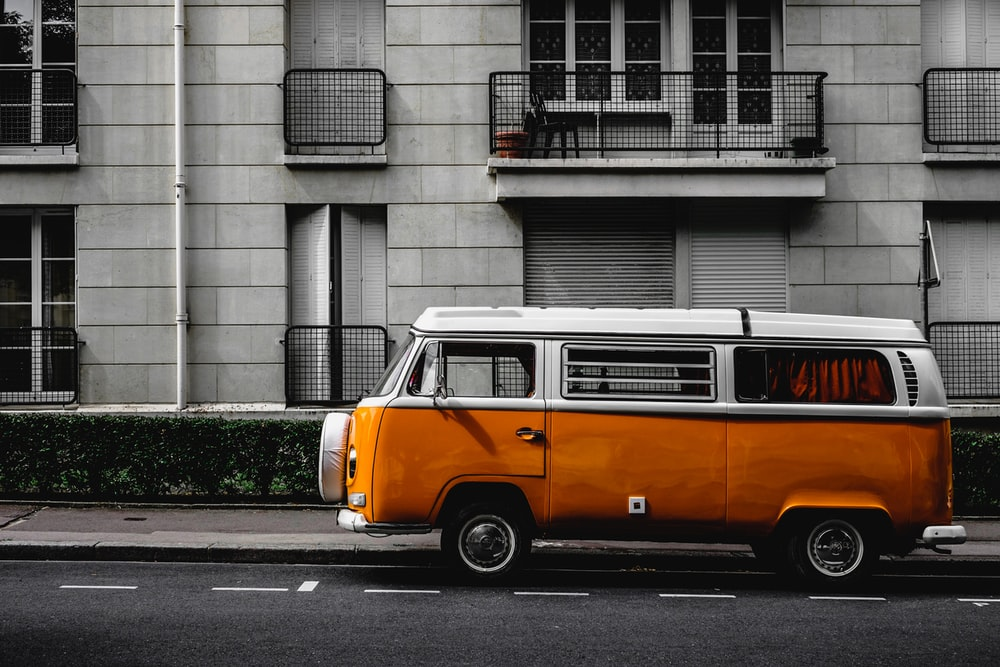 white and orange Volkswagen Kombi on road