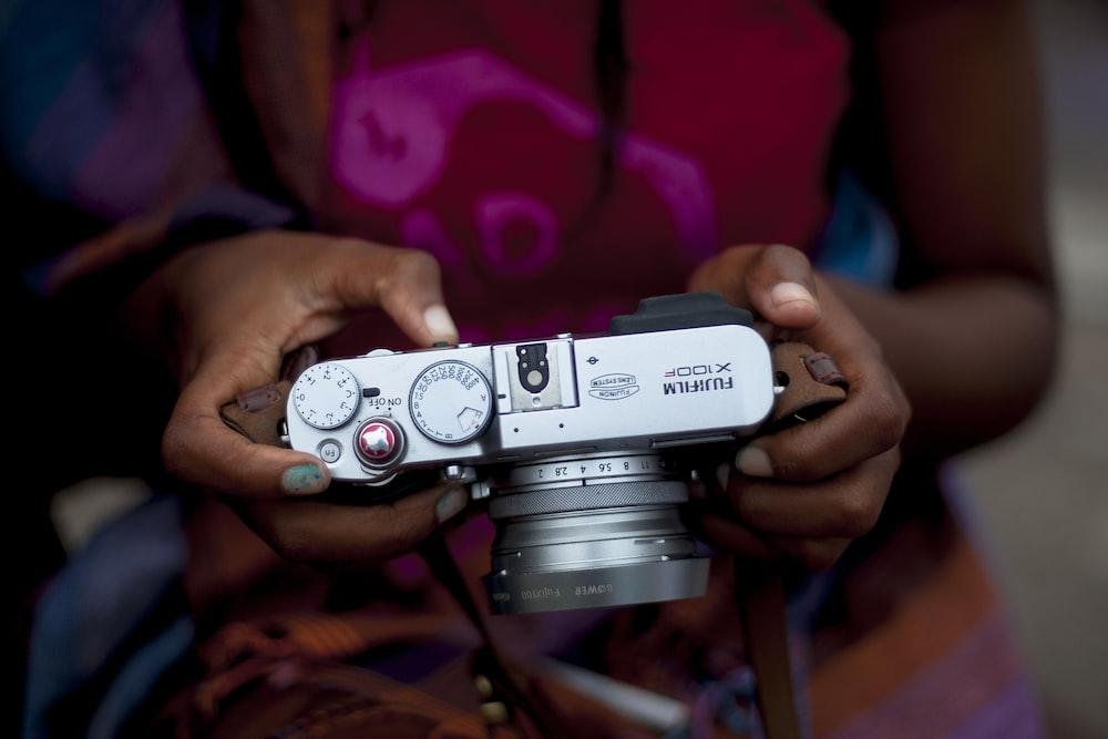 woman holding gray Fujifilm X100P