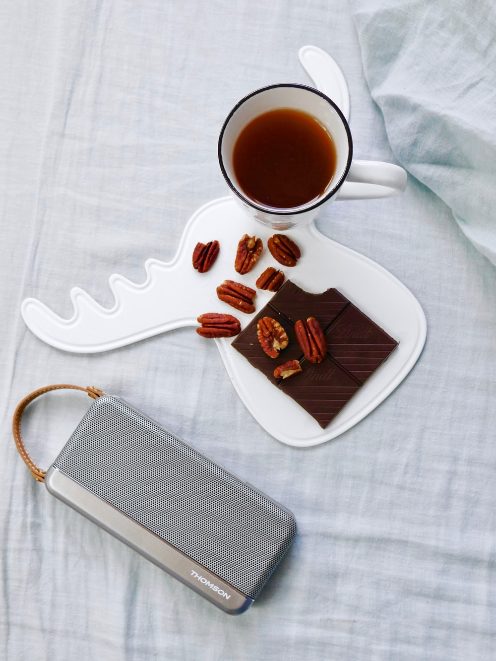 walnuts on white tray beside cup of coffee