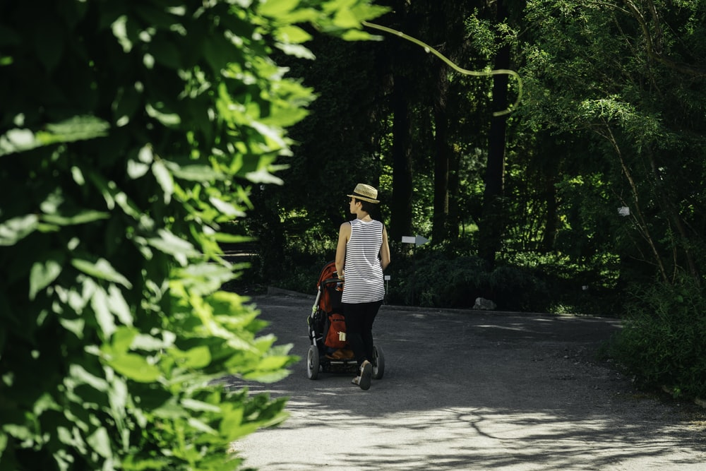 man in white and black long sleeve shirt riding red and black motor scooter during daytime