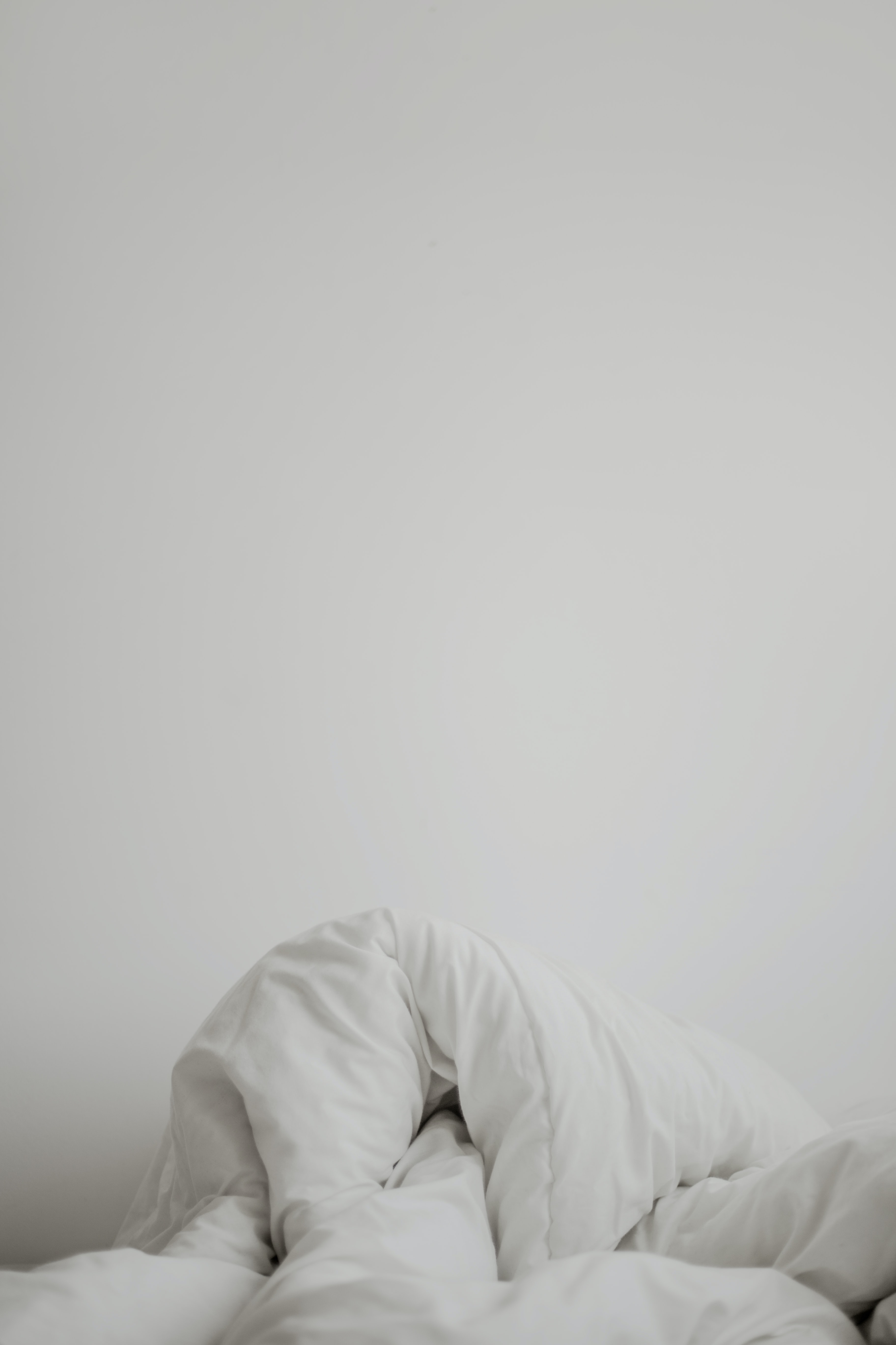 Messed up white blankets against a white wall.