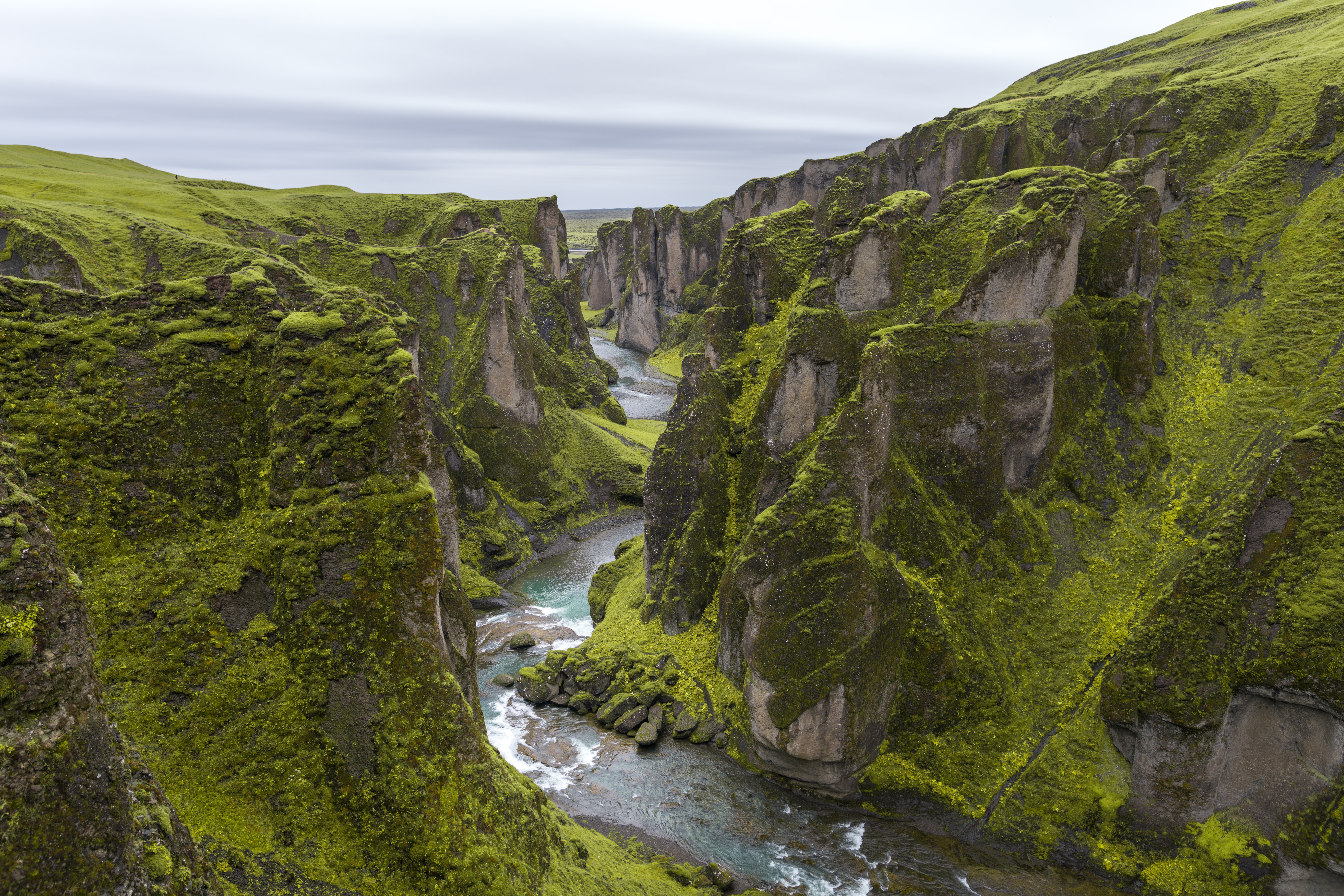 green mossy cliff with river in the middle
