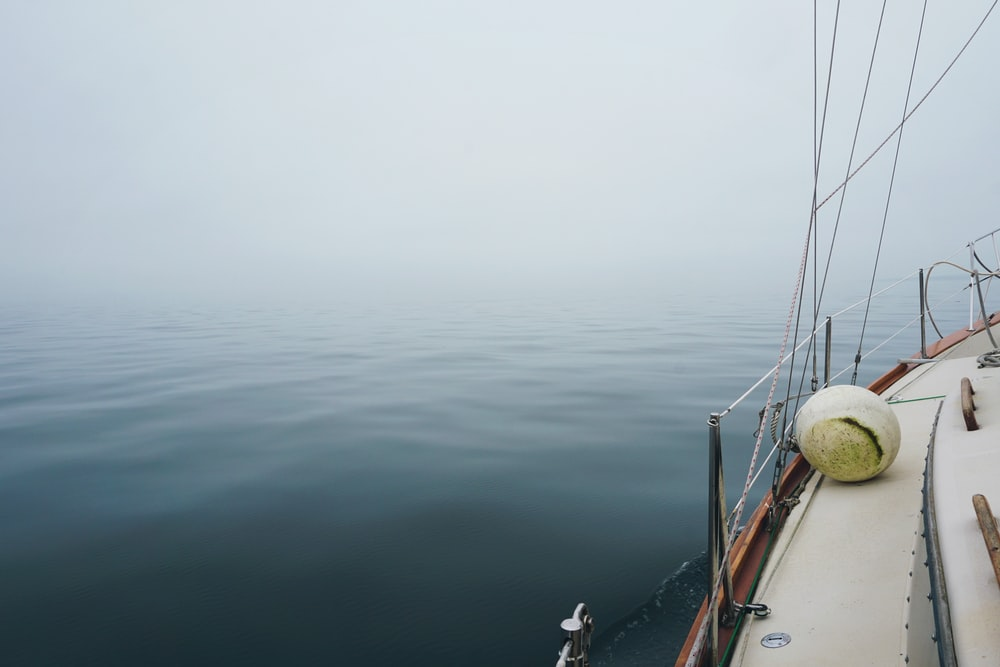 white sailboat on ocean with fog