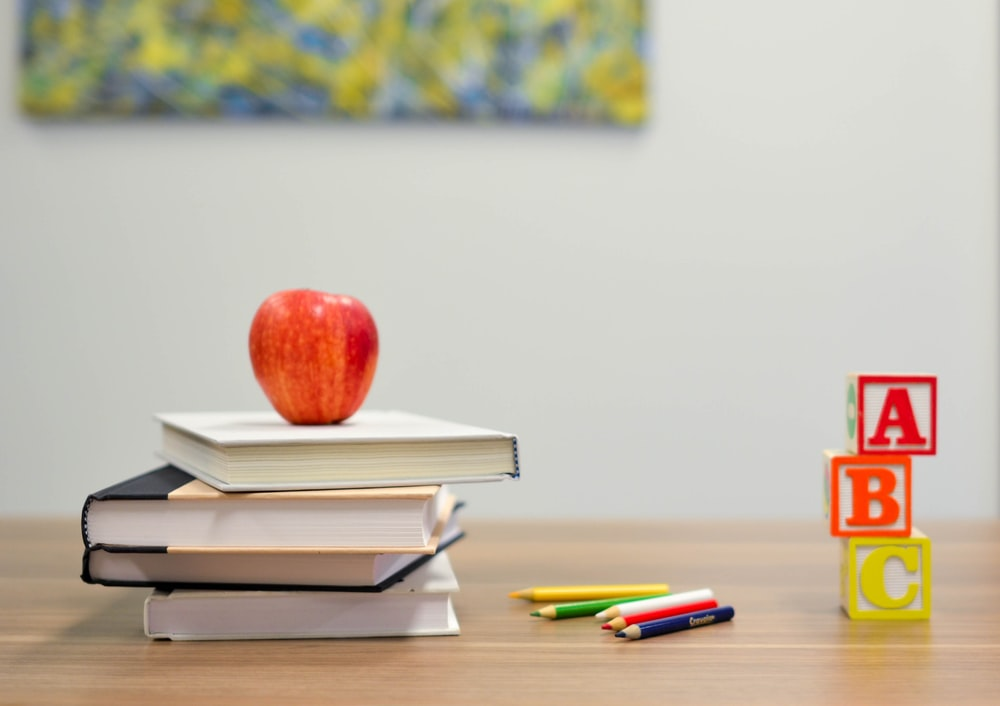 an apple on a pile of books, some colouring pencils, and some building blocks on a desk