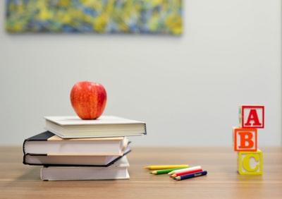 red apple fruit on four pyle books school zoom background