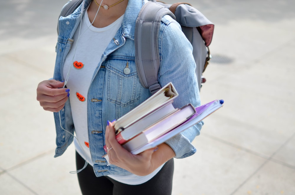 woman wearing blue denim jacket holding book