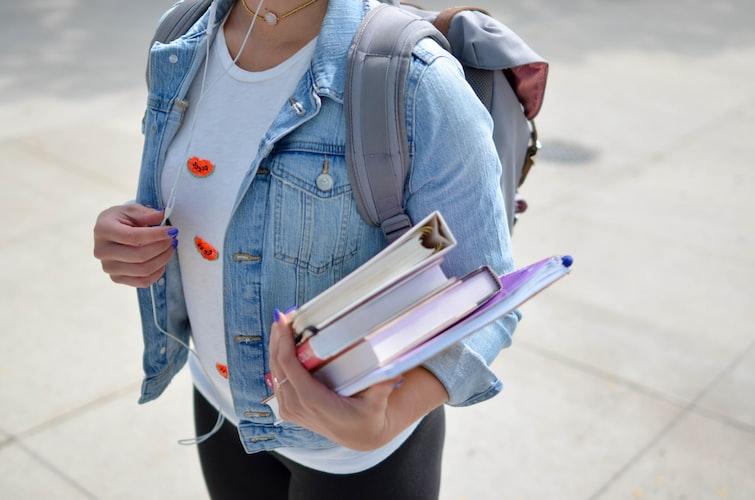 estudante vestindo jaqueta jeans e segurando livros