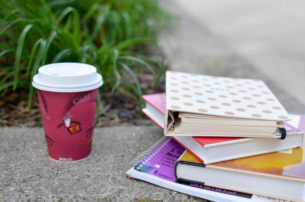 red and white cup beside book