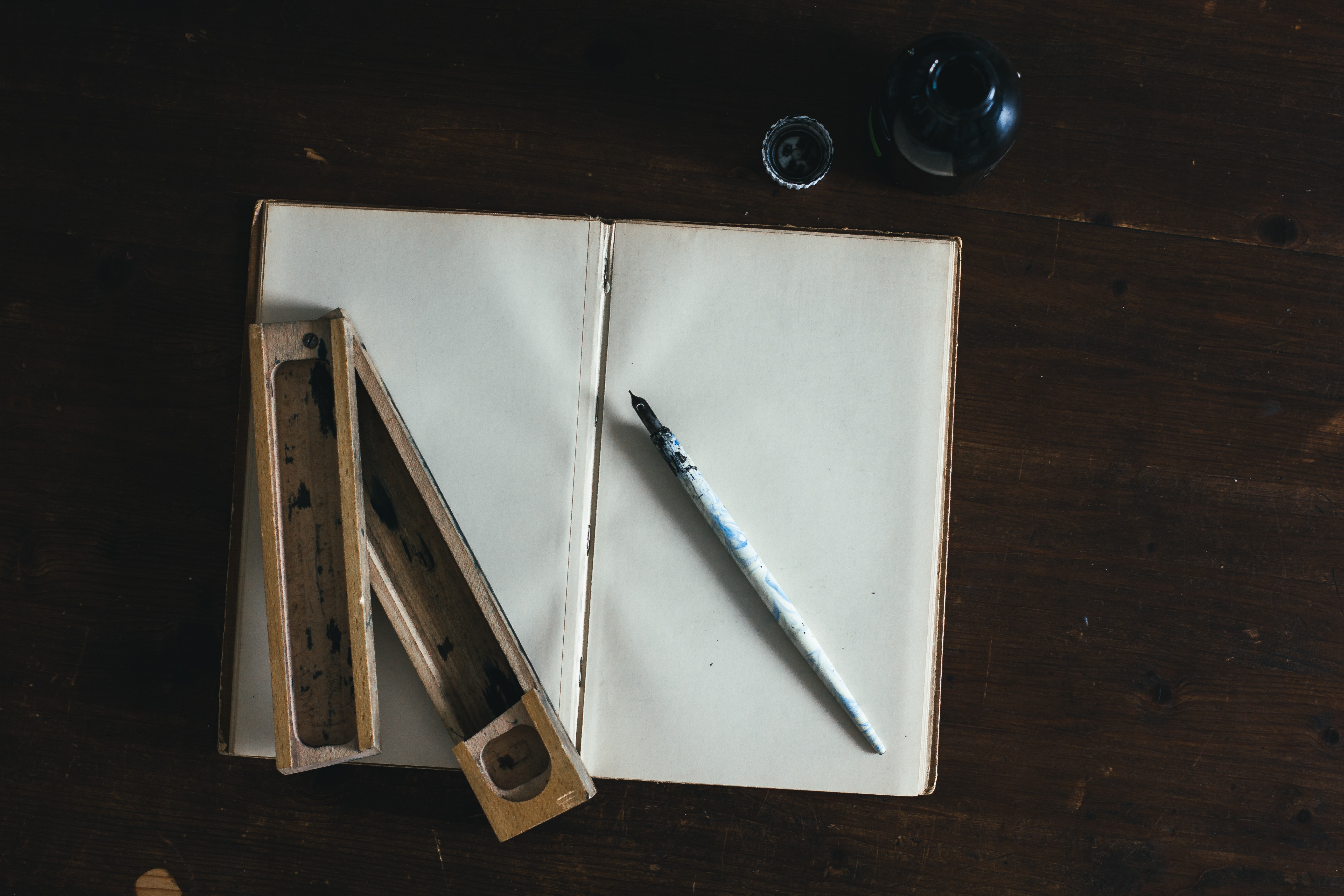 A sketchbook, calligraphy pen, ink pot and ink holder on a wooden table in Cologne